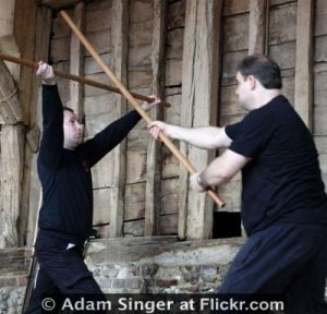 Two English Martial Arts Fighters With Quarterstaffs In A Barn